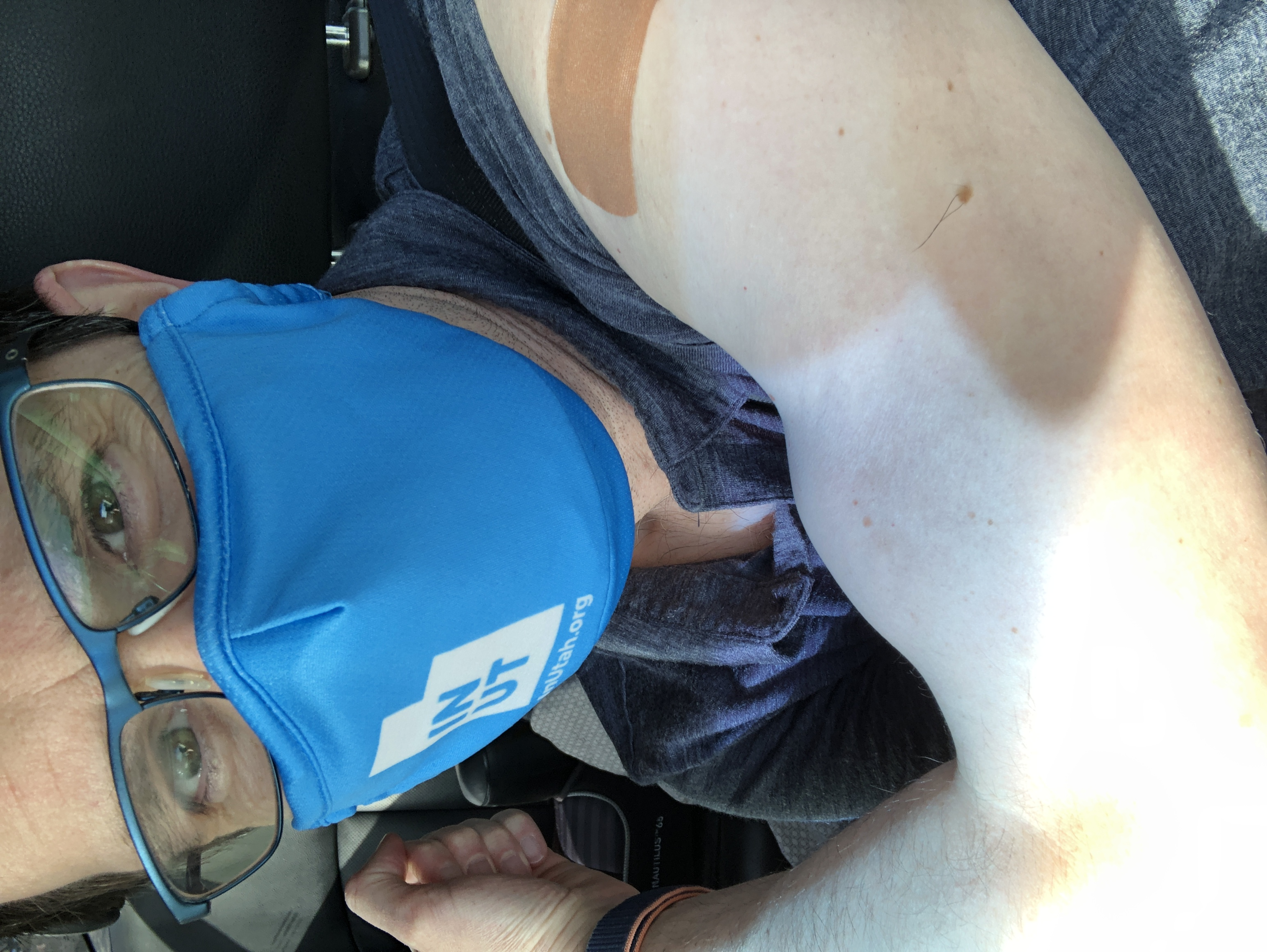 Self-portrait showing an arm with a band-aid on the shoulder, and a masked face