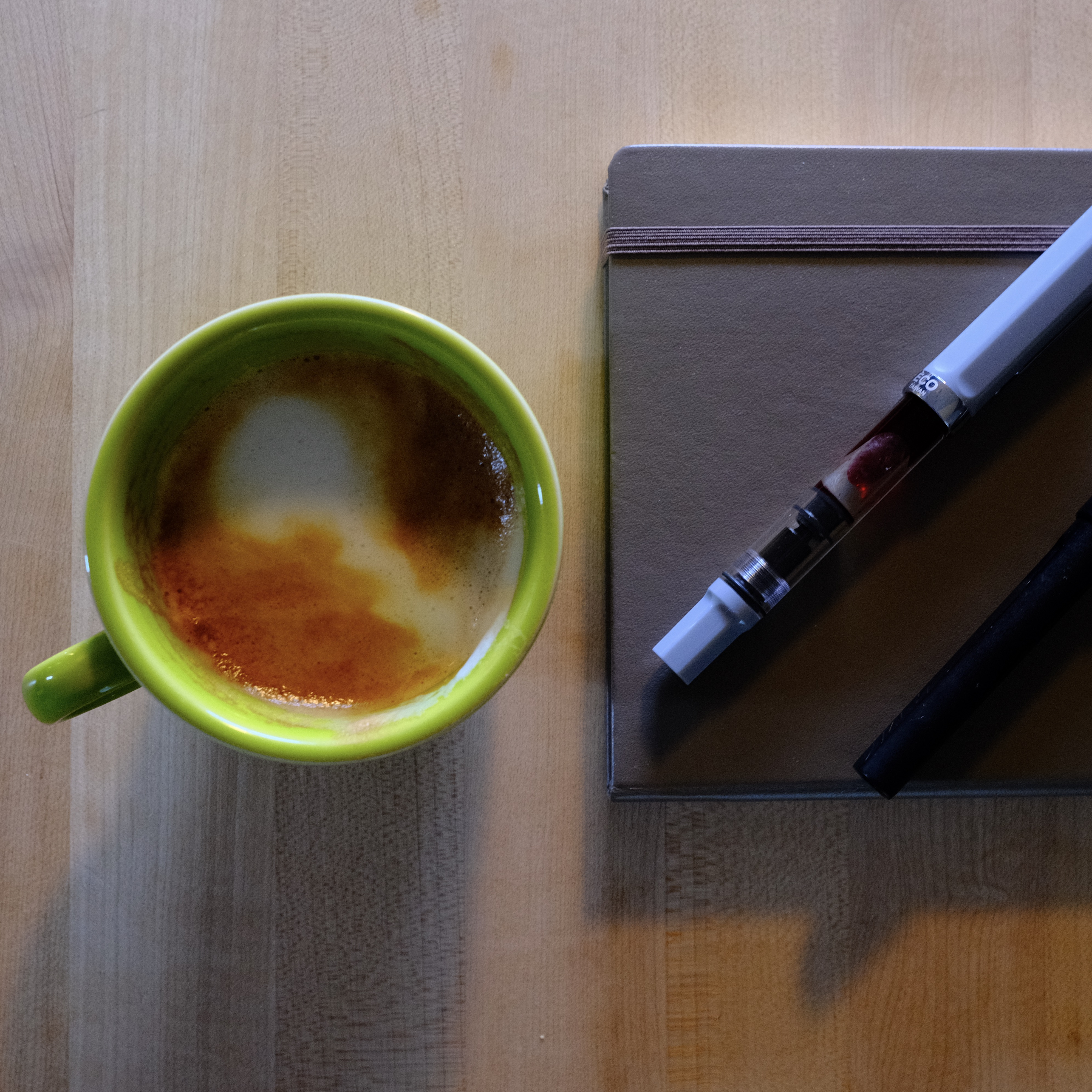 top-down photo of a cappuccino in a green mug, next to a brown notebook and ECO fountain pen with bright orange ink