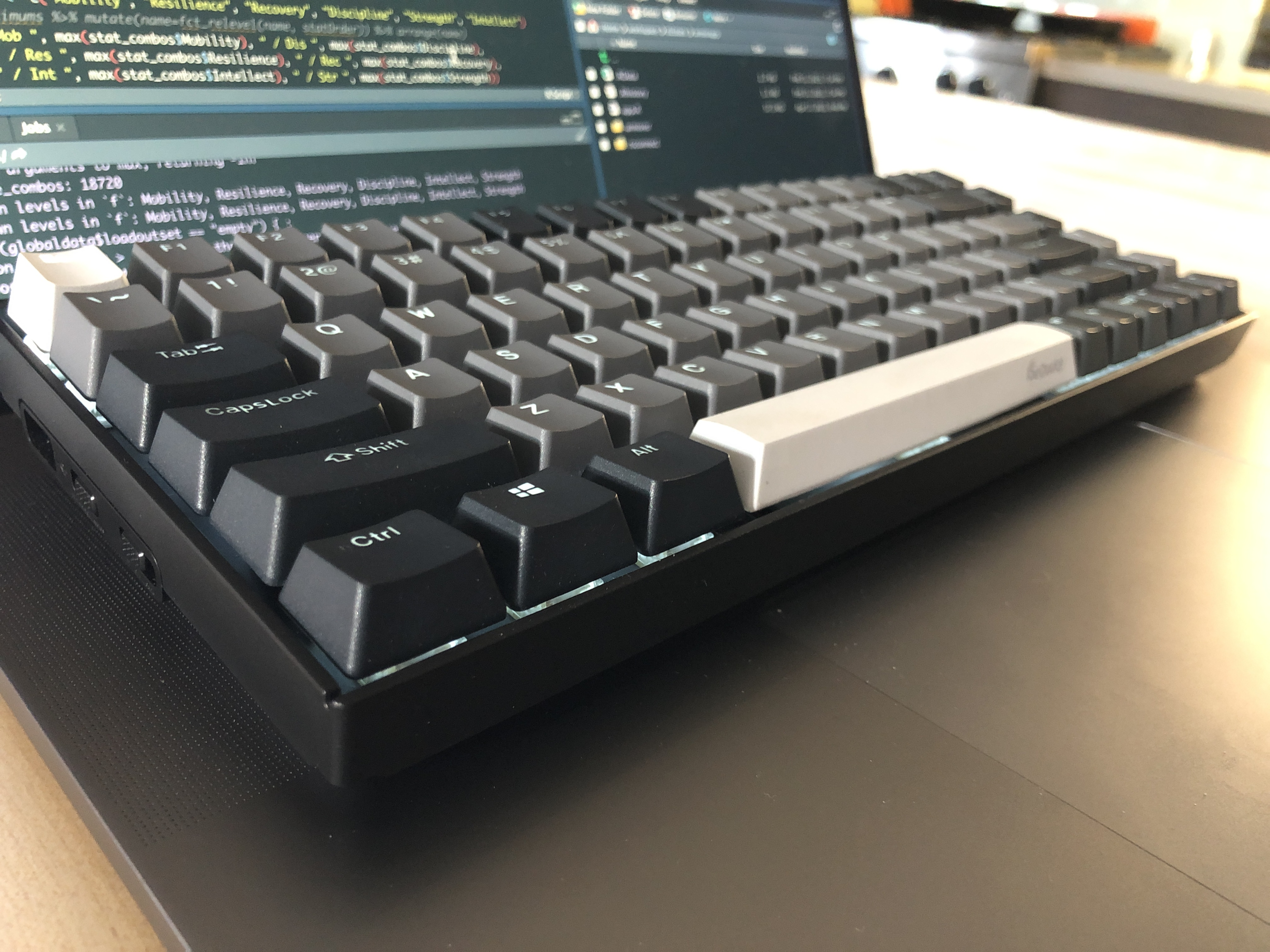 a mechanical keyboard with grey and white keys resting on top of a MacBook, viewed from an angle