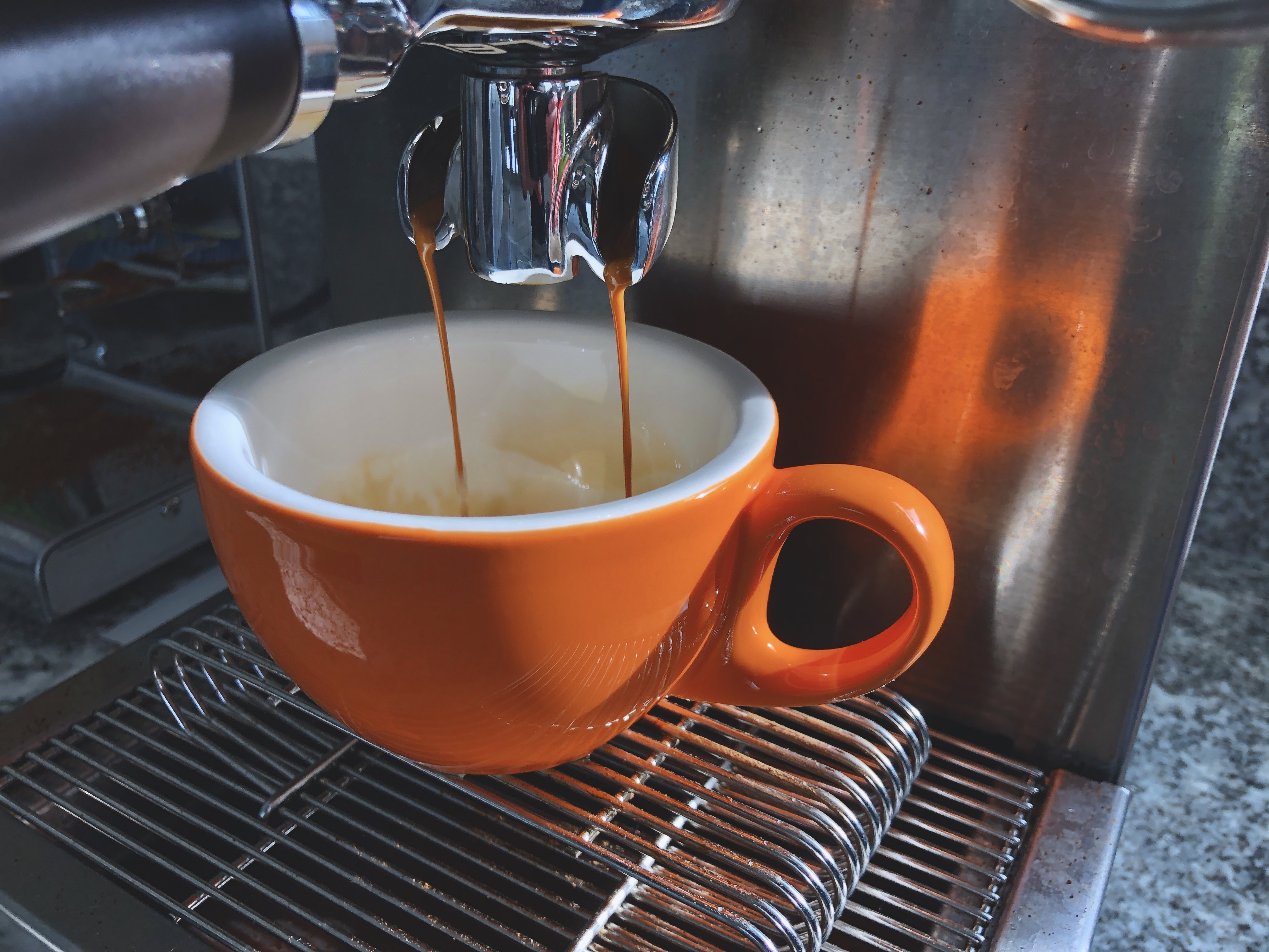 Espresso pouring from a shiny silvery brewhead into a bright orange and white cup