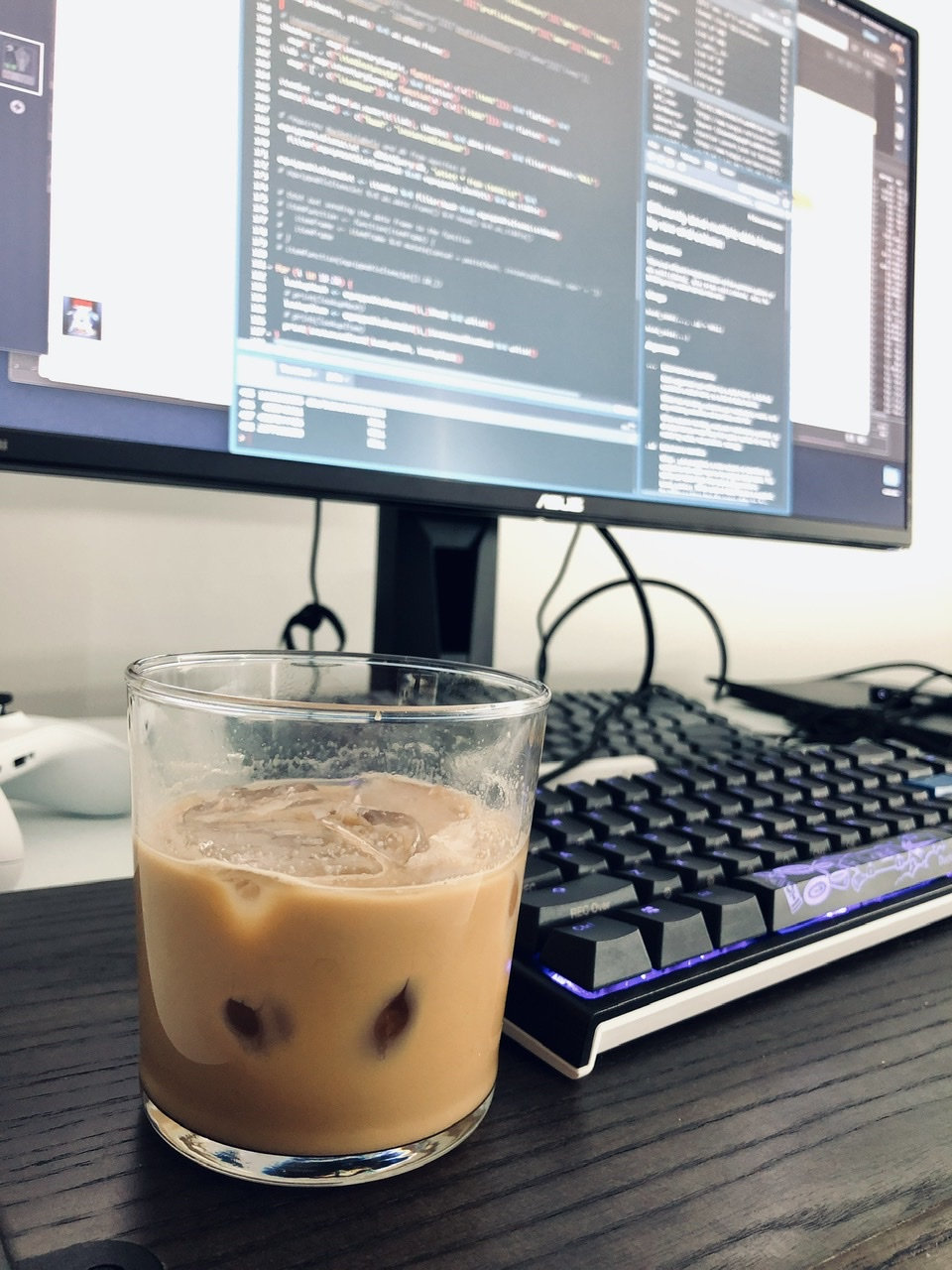 A glass of iced coffee beside a keyboard lit with purple LEDs