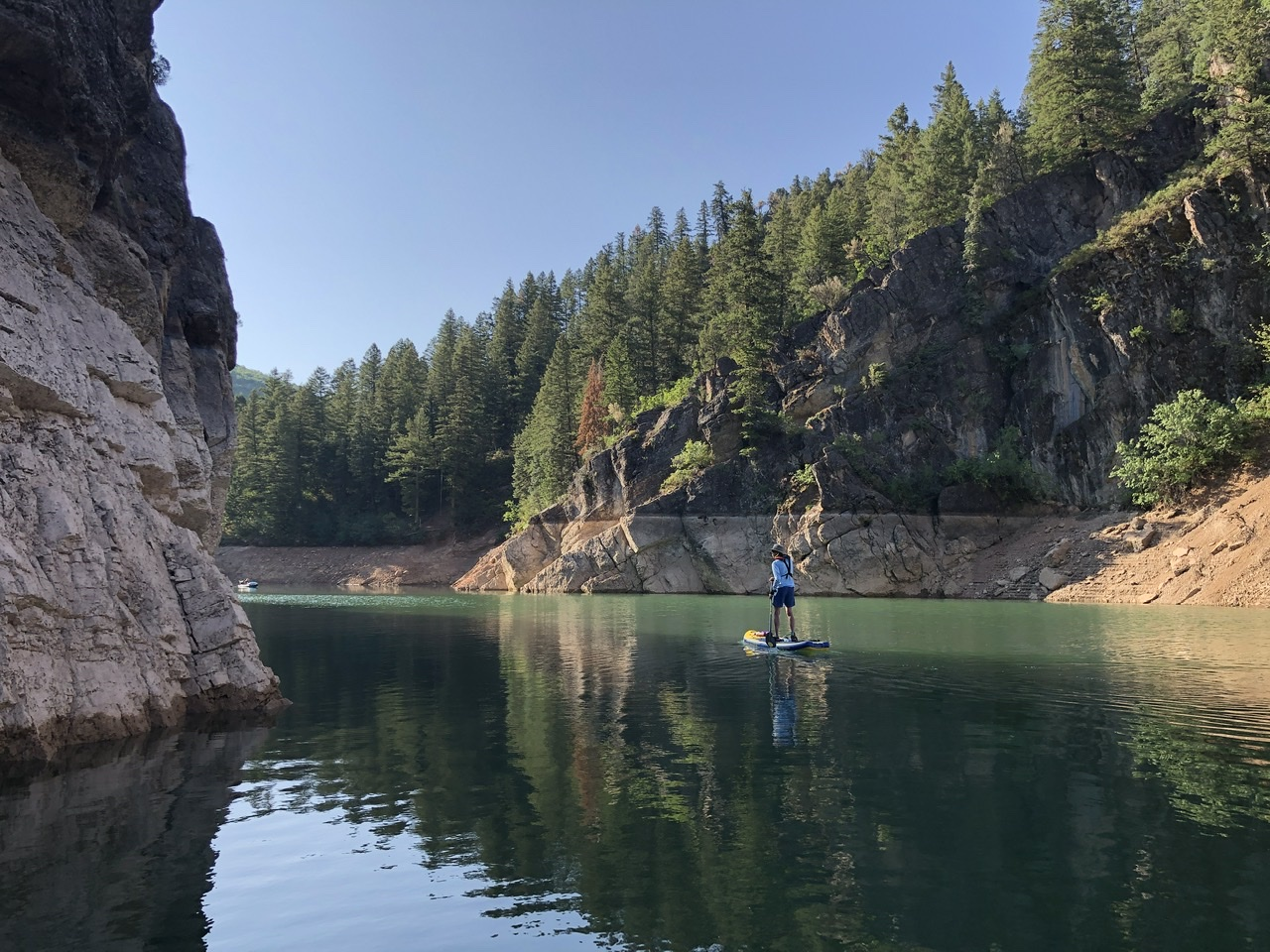 A man on a standing paddleboard, approaching a rocky turn in the water's path