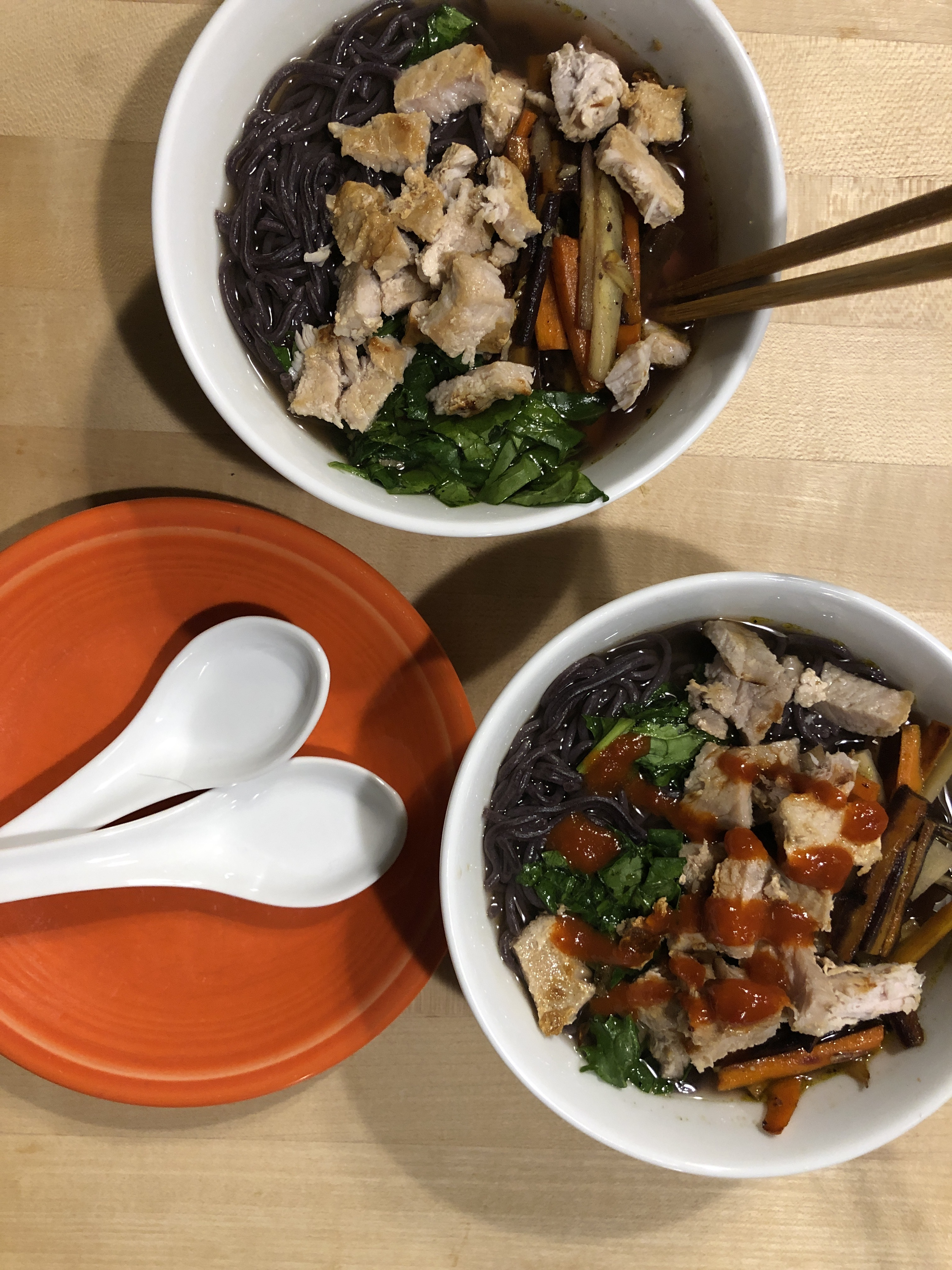 Two white bowls containing dark broth, rice noodles, chunks of pork and bright orange carrots
